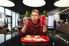 Young man eats fast food at a restaurant, sitting at a table. Tray of French fries and burger stock photos