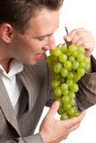 Young man eats green grapes Royalty Free Stock Image