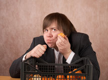 The young man eats tangerines Stock Photos