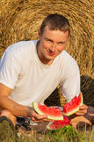The young man eats a tasty water-melon Stock Photography
