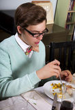 Young man eats Thanksgiving dinner turkey. Young boy sits at dinner table and eats holiday turkey stock images