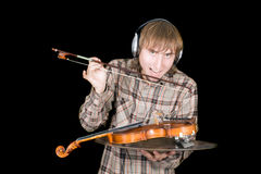 The young man eats a violin Stock Photography