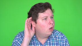 Young man eavesdropping and making funny facial expression on green screen stock video