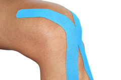 Young man with an elastic therapeutic tape in his knee Royalty Free Stock Photography