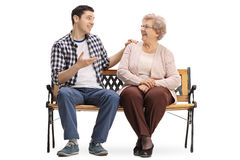 Young man and elderly woman sitting on bench and talking. Young men and an elderly women sitting on a bench and talking isolated on white background Royalty Free Stock Photo