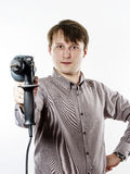 Young man with electric drilling machine isolated on white. Young man with drilling machine in his hands ready to professional constructing work Royalty Free Stock Images