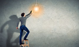 Young man with an electric light bulb Stock Images
