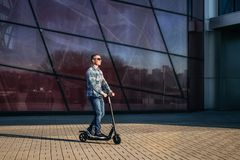 Young man on electric scooter on street. Man riding a electric kick scooter on stone pavement against modern glass wall of building royalty free stock photos