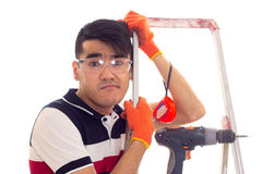 Young man with electric screwdriver and ledder. Disturbed young man with black hair in white and blue t-shirt and jeans with orange gloves and protective glasses Royalty Free Stock Image