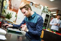 Young man in electronics workshop Stock Photography