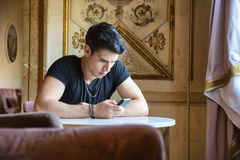 Young man in elegant place using cell phone Stock Images