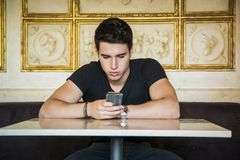 Young man in elegant place using cell phone. Young handsome man sitting in elegant cafeteria or restaurant using cell phone to send text message Royalty Free Stock Photos