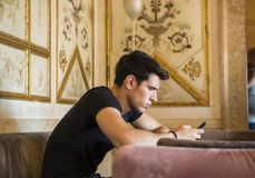 Young man in elegant place using cell phone Stock Image