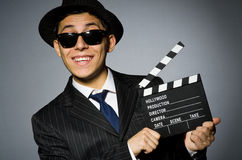 Young man in elegant suit holding clapperboard Stock Image