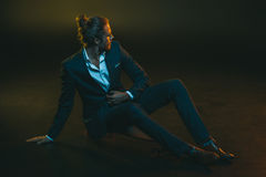 Young man in elegant suit sitting on skateboard. Stylish young man in elegant suit sitting on skateboard Stock Photography