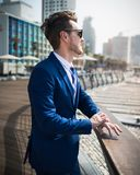 Young man in elegant suit and sunglass is relaxing on the nature. In warm sunny day. Successful manager on the background of the cityscape. Trendy guy stands on Stock Photo