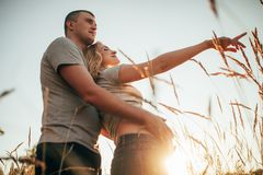 A young man embraces the belly of his pregnant wife against background of sky and spikelets. A young men embraces the belly of his pregnant wife during a walk royalty free stock image