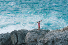 Young man embracing the ocean while standing on the cliff Royalty Free Stock Photos