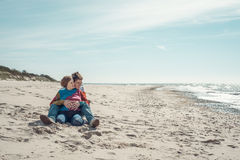 Young man embracing a woman sitting on the beach Stock Photos