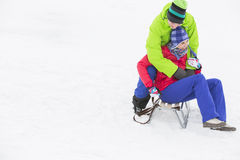 Young man embracing woman on sled in snow Stock Photos