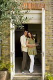 Young man embracing young pregnant woman in doorway, smiling, portrait Stock Images