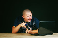 A young man emotionally playing computer games Royalty Free Stock Image