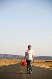 Young Man with Empty Gas Can. Young man walking down the middle of the highway with a red gasoline can because he is out of gas royalty free stock photos