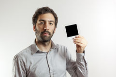 Young man with empty photo frame Stock Photos