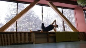 A young man is engaged in gymnastics on the windowsill of a large window. He leans on his elbow and one leg facing the