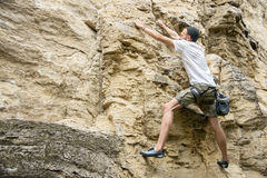 A young man is engaged in rock climbing on a steep rock without insurance Stock Images