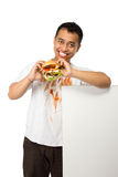Young man enjoy his burger beside a white plank Royalty Free Stock Images