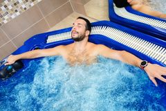 Young man enjoy and relax in spa center. Water,and massage,sauna,Swimming pool royalty free stock image