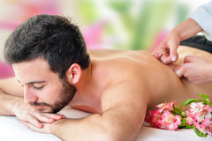 Young man enjoying back massage. Royalty Free Stock Photography
