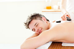 Young man enjoying a back massage with hot stones stock image