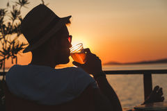 Young man enjoying at a beach bar. Young man enjoying sunset at a beach bar Royalty Free Stock Images
