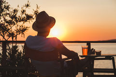 Young man enjoying at a beach bar. Young man enjoying sunset at a beach bar Royalty Free Stock Image