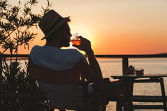 Young man enjoying at a beach bar. Young man enjoying sunset at a beach bar Stock Image