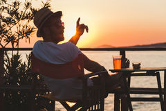 Young man enjoying at a beach bar. Young man enjoying sunset at a beach bar calling for waiter Royalty Free Stock Photo