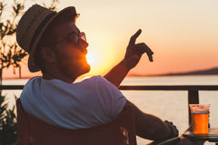 Young man enjoying at a beach bar. Young man enjoying sunset at a beach bar calling for waiter Stock Image