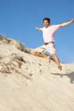 Young Man Enjoying Beach Holiday Running Down Dune. In The Sun Stock Photo