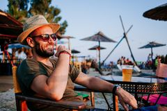 Young man enjoying beer in a beach bar. Young man enjoying beer and sunset in a beach bar stock photography