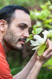 Young man enjoying the blossom of spring white magnolia flower. Stock Photos