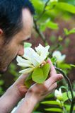 Young man enjoying the blossom of spring white magnolia flower. Stock Images