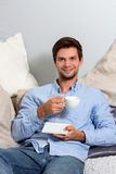 Young man enjoying a coffeebreak. Young brunette man in blue clothing enjoying a coffeebreak royalty free stock photo