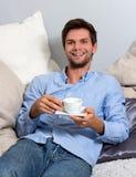 Young man enjoying a coffeebreak. Young brunette man in blue clothing enjoying a coffeebreak royalty free stock image