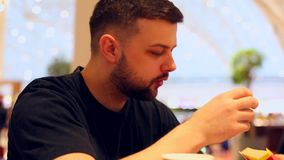 Young man is enjoying a delicious burger and french fries in the restaurant. Young man is enjoying a delicious burger and french fries in the restaurant stock video