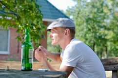 Young man enjoying a drink and cigarette Royalty Free Stock Image