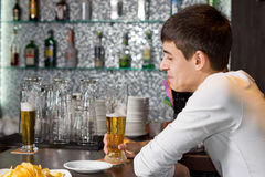 Young man enjoying a glass of beer with a friend Stock Photo