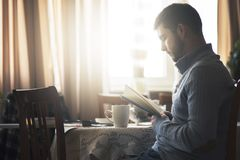 Man reading a book at his home. Young man enjoying a great piece of writing, a new bestseller, enjoying his hobby Royalty Free Stock Photo