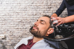Young man enjoying hairwash at beauty salon. Close up of hairdresser arms massaging human head during washing. Male client closed eyes with enjoyment Stock Photo